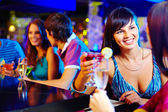 Girl with cocktail talking to her friend — Stock Photo