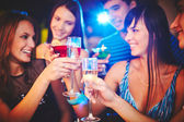 Girls and guys toasting at party — Stock Photo