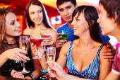 Girls and guys with martini and champagne — Stock Photo