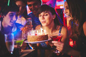 Girl blowing candles on birthday cake — Stockfoto