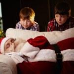 Boys looking at Santa Claus sleeping — Stock Photo #55486017