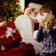 Brothers choosing gifts from sack with Santa Claus — Stock Photo #55486105