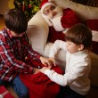 Boys choosing gifts from red sack — Stock Photo #55486225