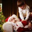 Boys trying to wake Santa up — Stock Photo #55486639