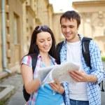 Couple of travelers studying map — Stock Photo #55488247