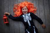 Girl in red wig holding lantern — Stock Photo