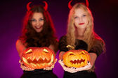 Halloween pumpkins held by females — Stock Photo