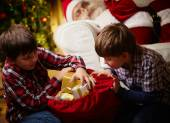 Boys choosing gifts with Santa Claus — Stock Photo