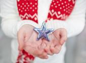 Human palms holding silver star — Stock Photo