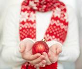 Xmas toy ball on hands — Stockfoto