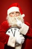 Santa holding Christmas clock — Stock Photo