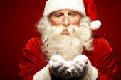 Santa Claus holding snow on palms — Stock Photo