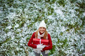 Girl in winter wear standing on grass — Stock Photo