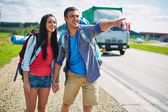 Young hitch-hikers standing by highway — Stock Photo