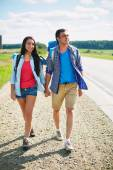 Hitch-hikers walking along highway — Stock Photo