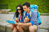 Young travelers eating fast food — Stock Photo