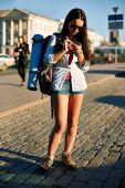Woman with backpack using cellphone — Stockfoto