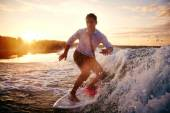Man in wet clothes surfboarding — Stock Photo