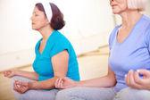 Aged females doing yoga — Stock Photo