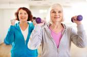 Sporty females doing exercising with barbells — Stock Photo