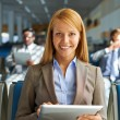 Woman with touchpad in airport — Stock Photo #58579661