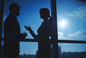 Businessman and businesswoman communicating by the window — Stock Photo