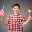 Boy holding bengal light and American flag — Stock Photo #58581065