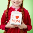 Girl holding gift for mother — Stock Photo #58581139