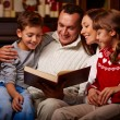 Family reading book on Christmas evening — Stock Photo #58584785