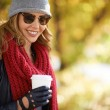 Woman drinking coffee in autumn park — Stock Photo #58585721