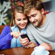 Couple using smartphone in cafe — Stock Photo #58586127