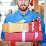 Man in Santa cap holding gift boxes — Stock Photo #58586487