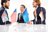 Business people with flags on negotiation table — Stock Photo
