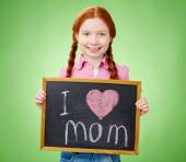 Girl holding blackboard with love declaration to mom — Stock Photo