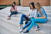 Girls reading book on stairs — Stock Photo