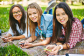 Girls with smartphones in park — Stock Photo