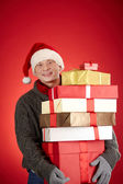 Santa man with pile of gift boxes — Stock Photo