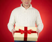 Man in white pullover holding gift — Stock Photo