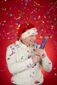 Man in Santa cap with confetti cracker — Stock Photo