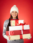 Girl in winter wear holding gifts — Stock Photo