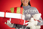 Woman holding Christmas packages and teddy bear — Stock Photo