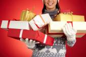 Smiling girl holding Christmas gifts — Stock Photo