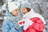 Couple holding cups with red hearts — Stockfoto