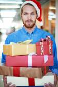Man in Santa cap holding gift boxes — Stock Photo