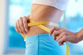 Sporty female measuring her waist — Stock Photo