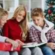 Family reading on Christmas evening — Stock Photo #59963875