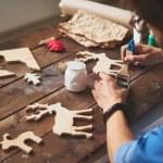Craftsman painting wooden deers — Stock Photo #59963999