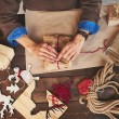 Male hands wrapping Christmas gifts — Stock Photo #59964121