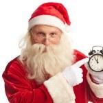 Santa pointing at alarm clock — Stock Photo #59964923