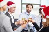 Business partners in Santa caps toasting — Stock Photo